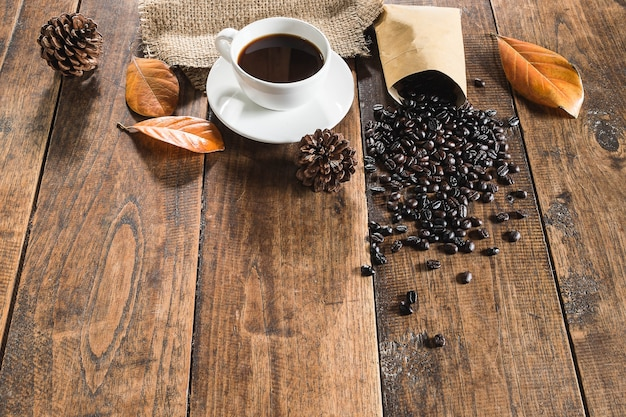 Copo de café de fundo e grãos de café no chão de madeira