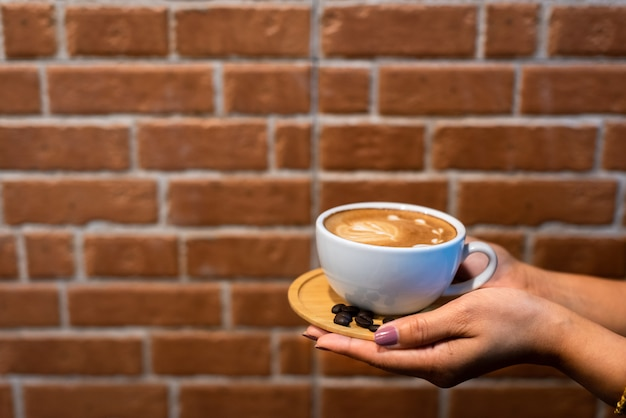 Copo de café de latte art nas mãos com fundo de parede de tijolo