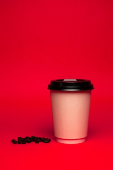 Copo de café de papel com grãos em um fundo vermelho