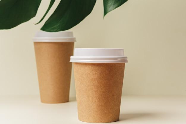 Copo de café de papel descartável e folha verde. conceito de ecologia