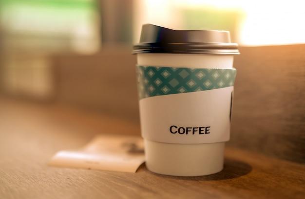 Copo de café de papel na cafeteria na mesa de madeira marrom