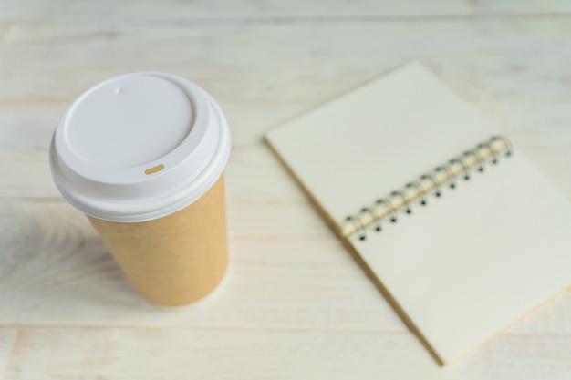 Copo de café de papel ofício e diário de caderno aberto com espaço de cópia na mesa de madeira