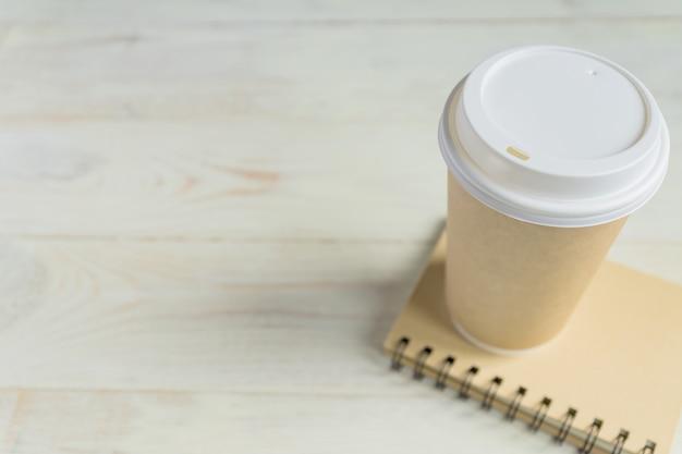 Copo de café de papel ofício e diário de notebook com espaço de cópia