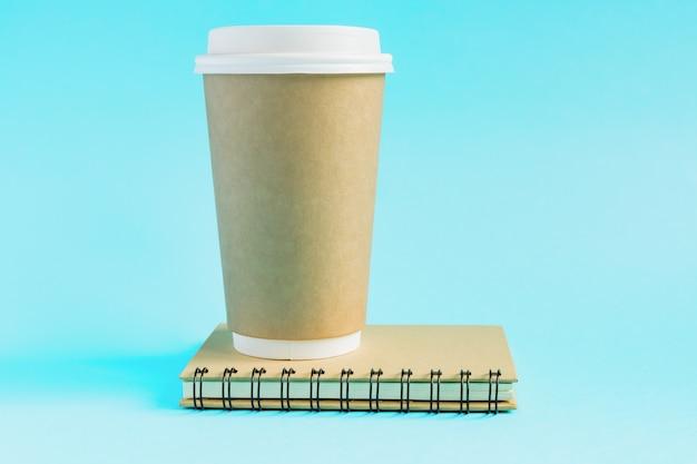 Copo de café de papel ofício e diário de notebook