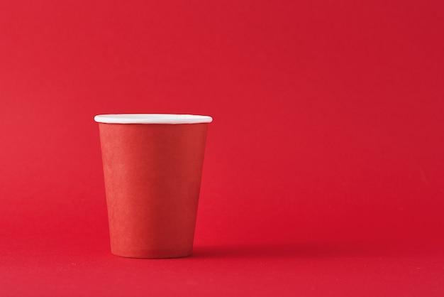 Copo de café de papel vermelho sobre fundo vermelho, com espaço de cópia. estilo minimalista