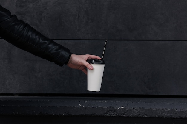 Copo de café descartável. mão segurando um café para viagem