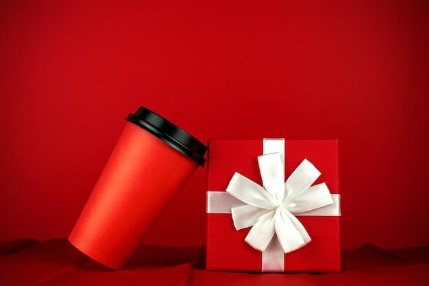 Copo de café descartável vermelho e caixa gidt na sala vermelha