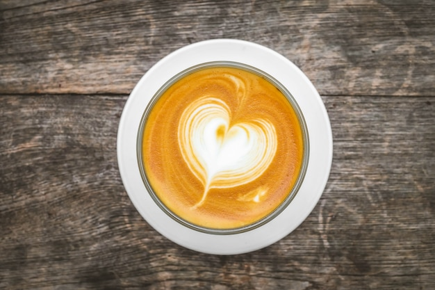 Copo de café do coração e grãos de café na superfície de madeira. vista do topo.