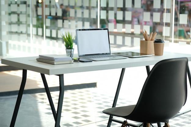 Copo de café do lápis da tabuleta do computador na mesa de escritório.