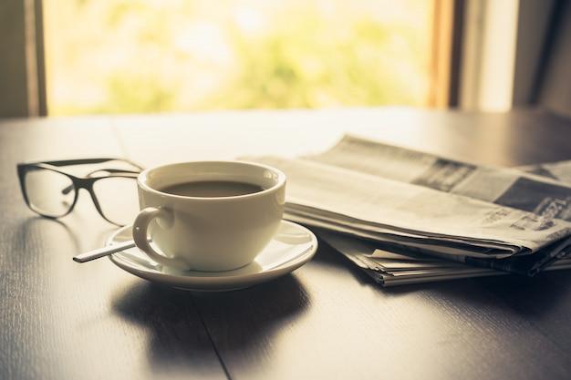 Copo de café dos vidros de leitura do jornal e telefone celular no fundo do jornal de negócio do mesa do negócio.