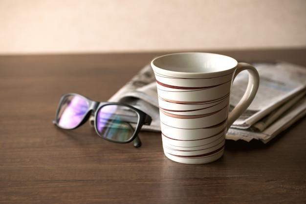 Copo de café dos vidros de leitura do jornal e telefone celular no jornal de negócios da mesa do negócio.