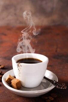 Copo de café e açúcar mascavado no fundo de pedra marrom.