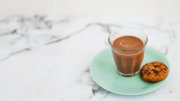 Copo de café e cookies único na placa turquesa sobre o pano de fundo de mármore
