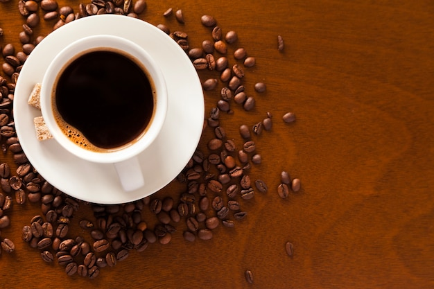 Copo de café e feijão na mesa de madeira