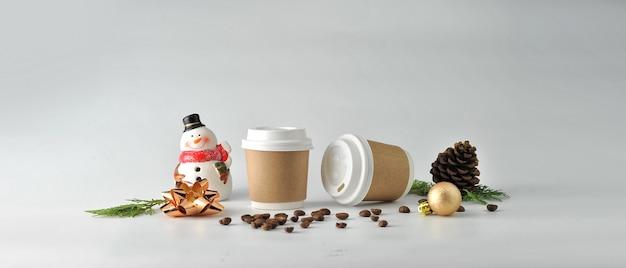 Copo de café e feijões de café de papel no fundo branco.