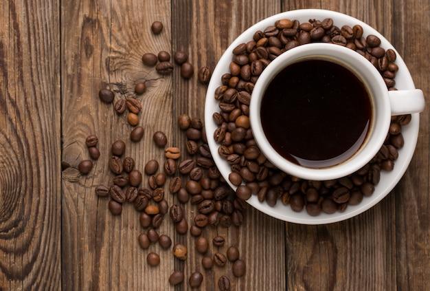 Copo de café e feijões de café no fundo de madeira.