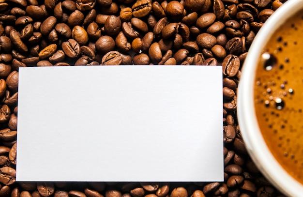 Copo de café e grãos de café na mesa, vista superior, café amor, grãos de café castanho isolado no fundo branco, copo de café quente com grãos de café