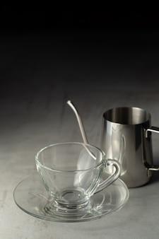 Copo de café e jarro de aço inoxidável sobre a mesa de cimento