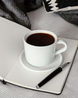 Copo de café e livro de ângulo alto