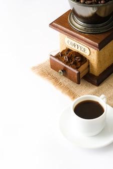 Copo de café e moedor de café isolado em um fundo branco.