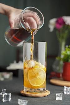 Copo de café expresso com suco de limão e fatias de limão fresco na mesa de madeira