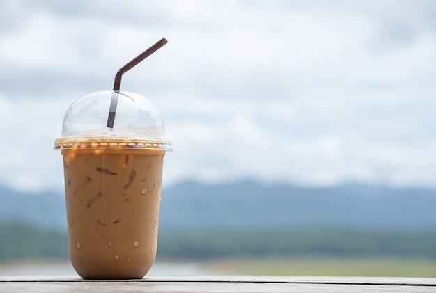 Copo de café expresso frio na mesa vistas embaçadas do fundo céu água e montanha.