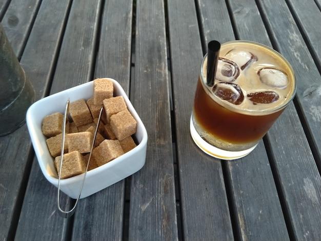 Copo de café expresso tônico coquetel com gelo e açucareiro com açúcar mascavo na mesa de madeira