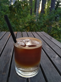 Copo de café expresso tônico coquetel com gelo na mesa de madeira no parque