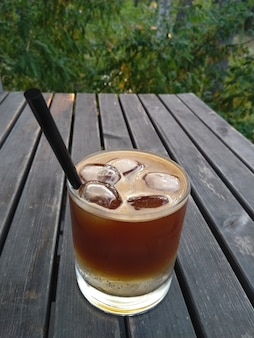 Copo de café expresso tônico coquetel com gelo na mesa de madeira no parque Foto Premium