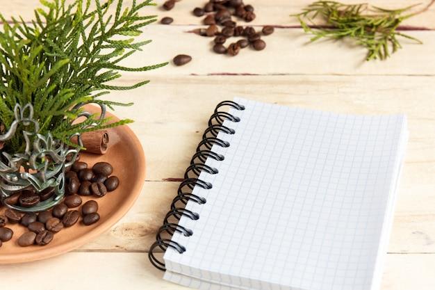 Copo de café, feijões de café e ramos spruce no fundo de madeira.