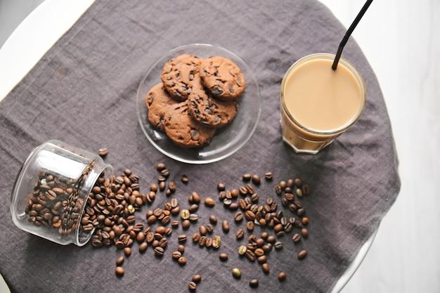 Copo de café frapê saboroso com biscoitos e feijão na mesa