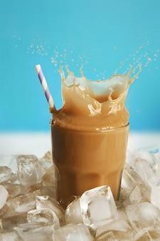 Copo de café frio com cubos de gelo e respingos na mesa