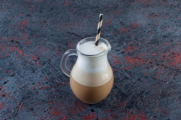 Copo de café frio espumoso com canudo na superfície de mármore.