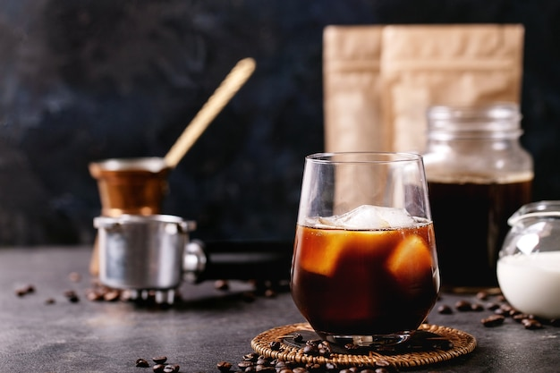 Copo de café gelado com cubos de gelo servido com creme, cezve de cobre e grãos de café sobre parede escura