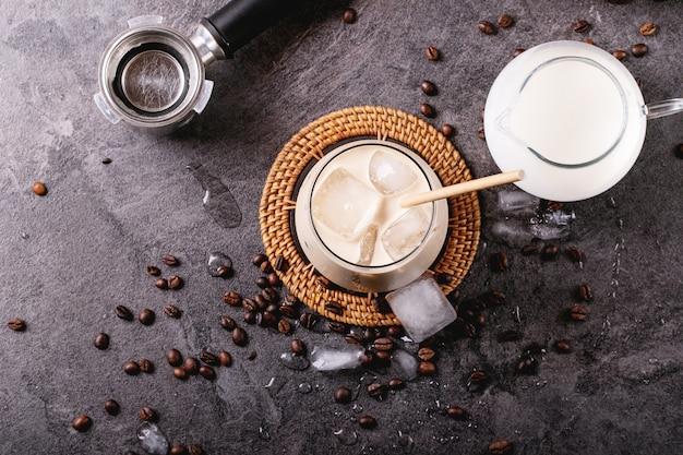 Copo de café gelado com cubos de gelo servido com creme e grãos de café sobre uma superfície escura. vista superior, configuração plana. copie o espaço