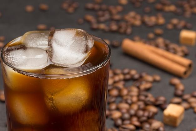 Copo de café gelado. no fundo preto, grãos de café, pau de canela, anis estrelado