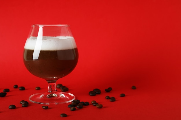 Copo de café irlandês e sementes de café em fundo vermelho