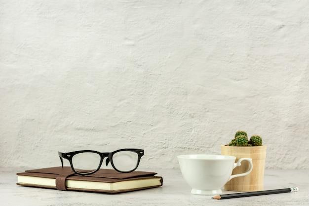 Copo de café, lápis e um caderno de couro na mesa com espaço da cópia.