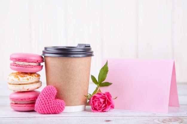 Copo de café, macarons e coração rosa de malha