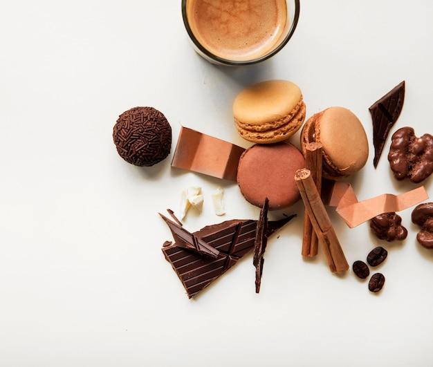 Copo de café; macaroons e pedaço de chocolate com ingredientes em fundo branco
