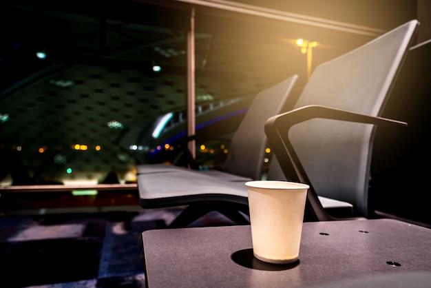 Copo de café na cadeira de mesa no aeroporto internacional.