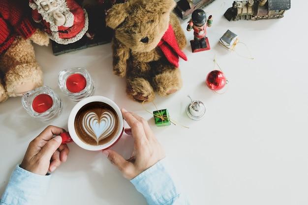 Copo de café na mão, colocado sobre a mesa.