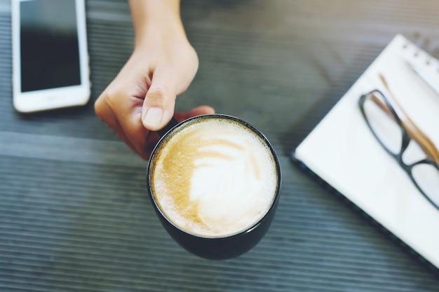 Copo de café na mão mulher de negócios pronta para beber na manhã de trabalho. mesa de mesa de escritório com bloco de notas de livro, telefone,