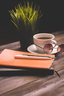 Copo de café papelaria bloco de notas trabalho mesa de madeira flor em vaso.