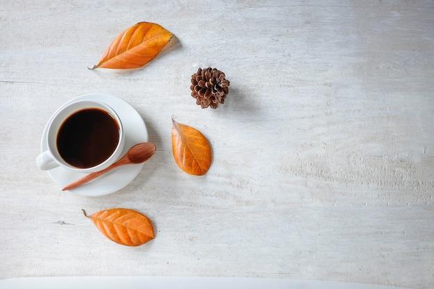 Copo de café preto e folhas secadas em um fundo branco.
