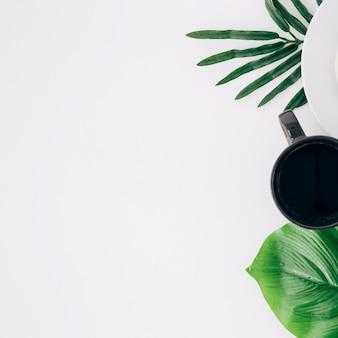 Copo de café preto e folhas verdes sobre fundo branco, com espaço de cópia para escrever o texto