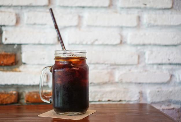 Copo de café preto gelado em pote na mesa de madeira com tijolo de parede