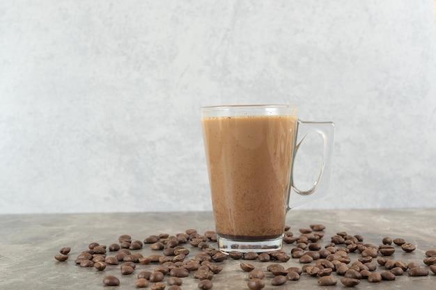 Copo de café quente e grãos de café na mesa de mármore