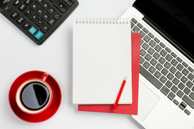 Copo de café vermelho, calculadora, bloco de notas em espiral, lápis no laptop sobre o fundo branco