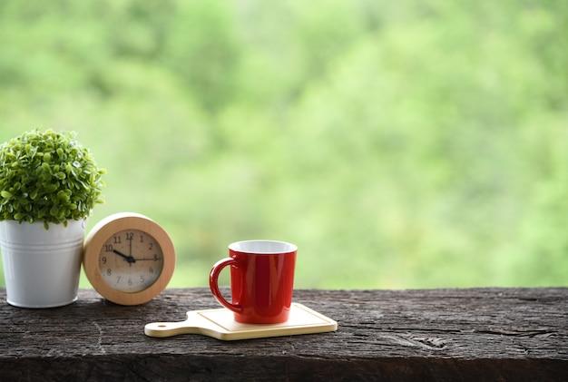 Copo de café vermelho sobre a velha mesa de madeira manhã verde natureza fundo